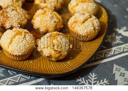Salty muffins with sausage and cheese on big brown plate on gray tablecloth with deers and smowlakes.