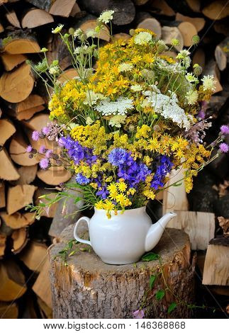 Beautiful bouquet of bright wildflowers standing on the stump