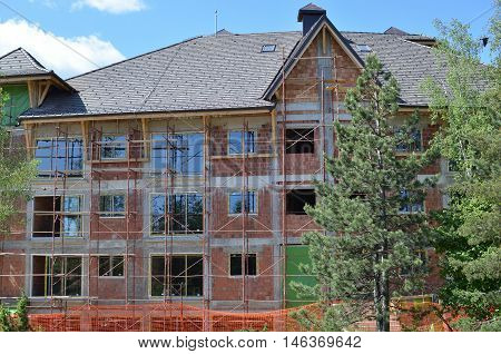 Close up of building on construction yard with scaffolds installed on exterior part of brick walls