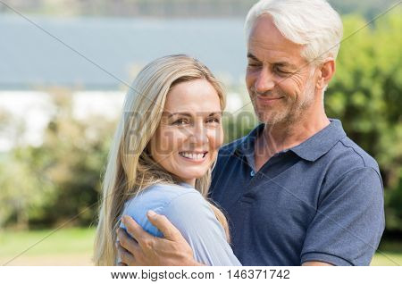 Senior couple relaxing outside house. Senior man looking with love his wife. Portrait of mature man looking at camera with her husband.
