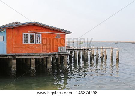 Traditional wooden house of fisherman in orange built on concrete stilts with blurred sea background, Thailand