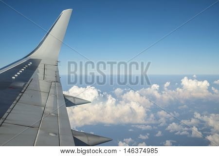 Aircraft wing view of cloudy blue sky from aircraft windows