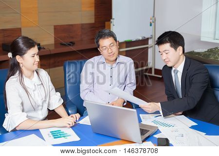 Business meeting Asian people sitting for a table with business plan on high floor in the office. Asian nationality male in suit shows a business graph of his business partner.