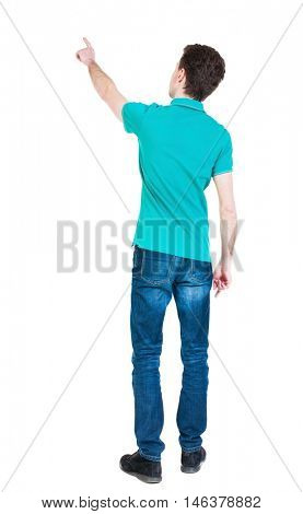 Back view of  pointing young men in  shirt and jeans. Young guy  gesture. Rear view people collection.  backside view of person.  Isolated over white background. The guy in a stylish T-shirt shows a