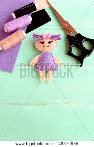 Handmade doll, scissors, thread set, needle, felt sheets on wooden background with copy space for text. How simply and cheaply make a kids toy. Cute doll crafts with felt for kids