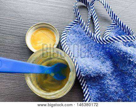 Empty baby food jar next to bib
