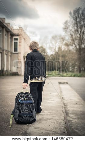 boy sadly goes to school with a heavy backpack
