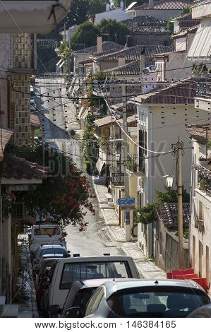 the street is in the mountains with low houses which are tightly to one another with the paved road parked cars across the street from house to house slung wires with light bulbs Delphi Greece