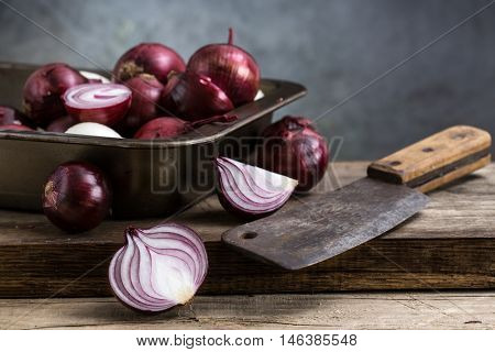 red onion on a plate and knife on a wooden board. still life