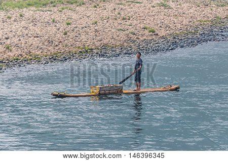 Yangshuo China - October 20 2013: Vendor on his floating market raft on the Li River near Yangshuo China.