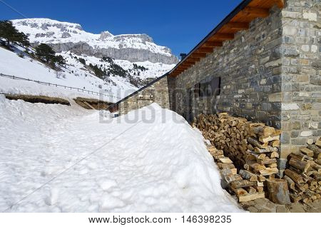 Stone house in a snowy landscape, Pyrenees, Spain,