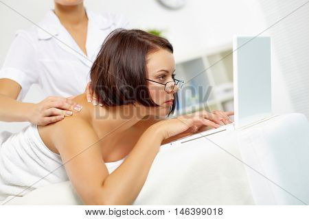 Young businesswoman lying on massage table and working on computer