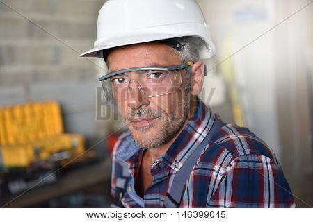 Portrait of metalworker with security helmet in workshop