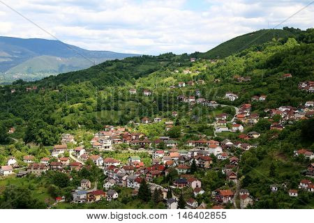 Scenic hill town of Jajce in Bosnia and Herzegovina Republic with sun light piercing through dark clouds shing on the hills