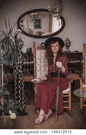 beautiful young model in a vintage costume (hat and gloves) with umbrella sits in vintage interior. photo toned vintage style