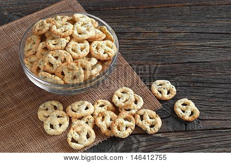 Salty pretzels with cheese and seed in glass bowl on wooden table. Tasty snack for beer