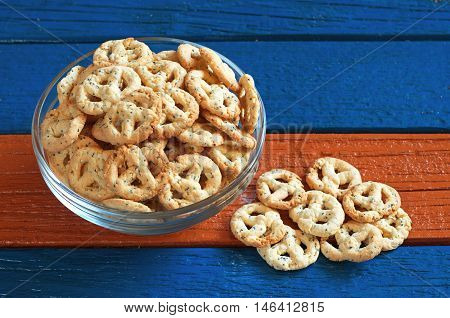Salty pretzels with cheese and seed in glass bowl on colorful wooden table. Tasty snack for beer