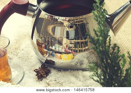Christmas tea pot with glass of tea with teddy bear reflection