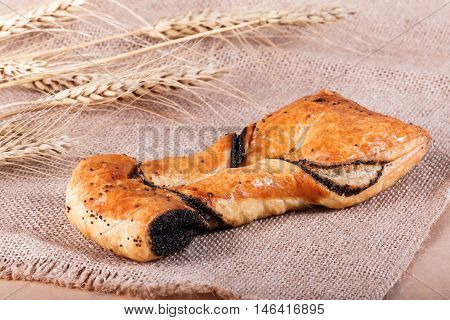 Sweet Puff Pastry With Poppy On Rustic Background With Spikelets