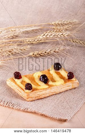 Fresh Puff Pastry With Powdered Sugar With Jam And Cream On Rustic Background With Spikelets