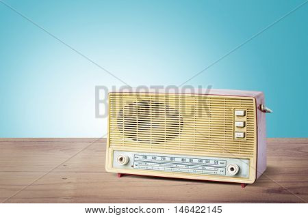 Old Dusty Radio From 1970 On Wooden Table With Blue Background.