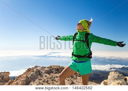 Woman successful hiker climbing camping in mountains motivation and inspiration landscape on island and ocean. Female hiker with arms up outstretched looking at beautiful view on Tenerfie Spain.