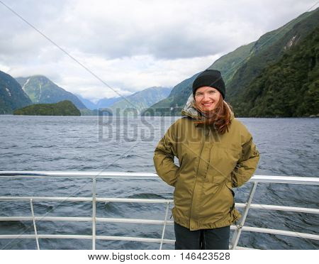 Young smiling woman standing on the deck of touring boat. Picturesque view of Milford Sound at Te Anau. Fiordland National Park New Zealand.