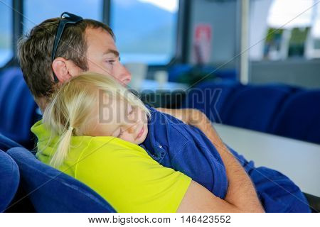 Young Father With Small Daughter Sleeping On His Shoulder. Lake Te Anau, New Zealand