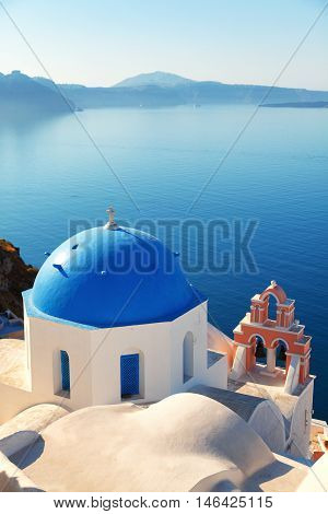 Blue dome church in Oia Santorini Greece. Sea and volcano on background