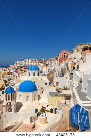 Landscape of Oia town in Santorini Greece with blue dome churches and small doors on foreground