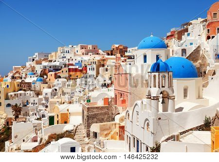 Landscape of Oia town in Santorini Greece with blue dome churches on foreground. Horizontal shot