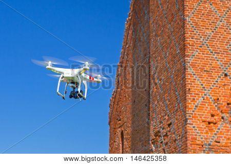 GRUDZIADZ, POLAND - AUGUST 27 ,2015: Flying drone quadcopter Dji Phantom 2 with digital camera GoPro HERO4 filming ruins of the castle.