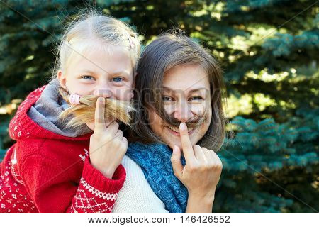 Funny family! Beauty funny girl holding hair - mustache. Beautiful young woman holding hair - mustache.