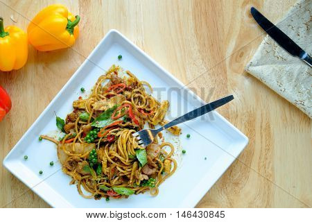 Fusion food Spaghetti spicy on wood table.
