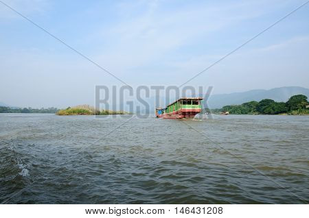 A wooden boat on the Mekong River in the Golden Triangle area of Thailand on a sunny day.
