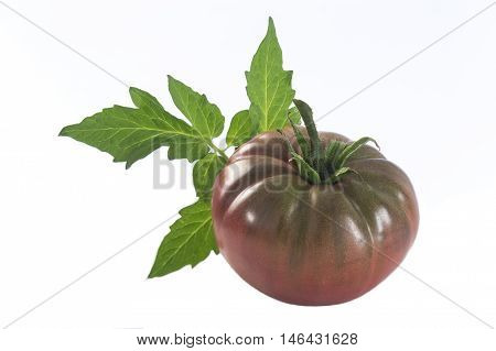 an isolated dark red heirloom tomato with leaf