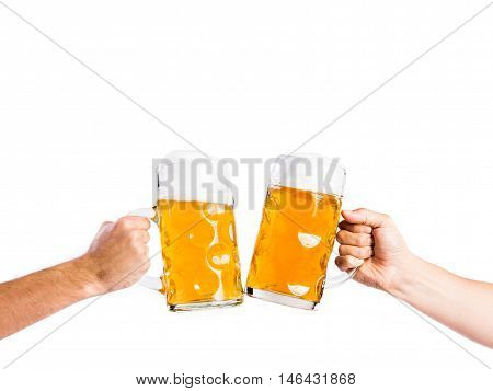 Hands of two unrecognizable men clinking with beer mugs. Oktoberfest. Studio shot on white background, isolated. Copy space.