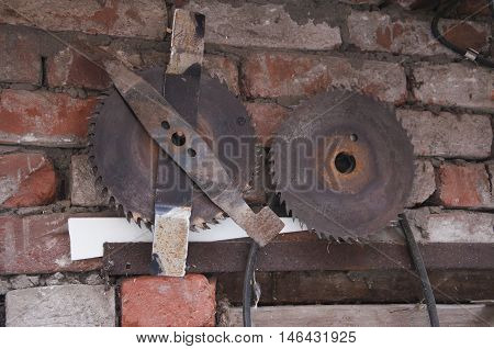 old circular saw on a brick wall