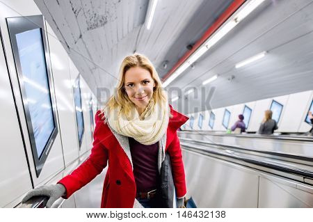 Beautiful young blond woman in red coat standing at the escalator in Vienna subway