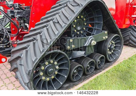 Rubber caterpillar farm tractor close up. Industry