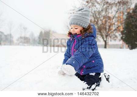 Beautiful little girl building a snowman, playing outside in winter nature