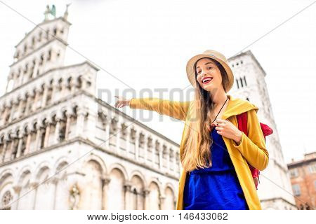Young female traveler in yellow sweater and hat pointing on San Michele basilica in Lucca old town in Italy. Having great vacations in Lucca