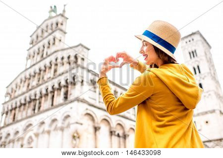 Young female traveler in yellow sweater and hat showing heart shape in front of San Michele basilica in Lucca old town in Italy. Having great vacations in Lucca