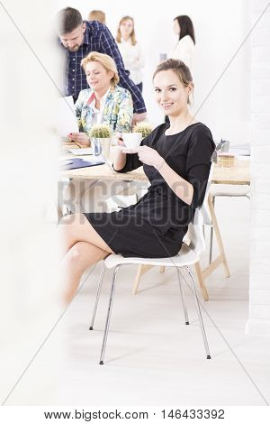 Young manager drinking coffee during a lunchbreak in a bright office