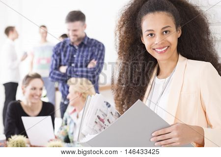 Portrait of a young dark-skinned woman in a modern office holding a portfolio with photos
