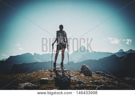 Rear view of hiker with poles near summit of mountain with dark vignette surrounding her