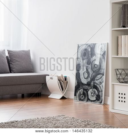 Room with carpet flooring sofa bookcase and modern pendant lamp.