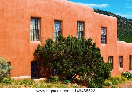 Historic adobe style building with mountains beyond taken in Santa Fe, NM