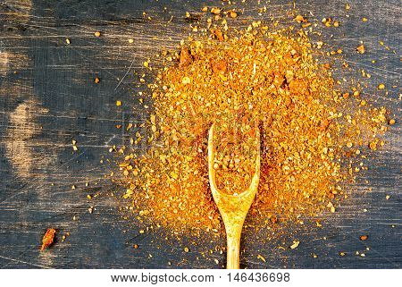 Seasoning. A mixture of spices for cooking, with a wooden spoon for spices on a black wooden table. top view, copy space