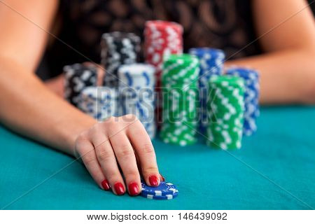 Woman betting gambling chips. Focus on hand.